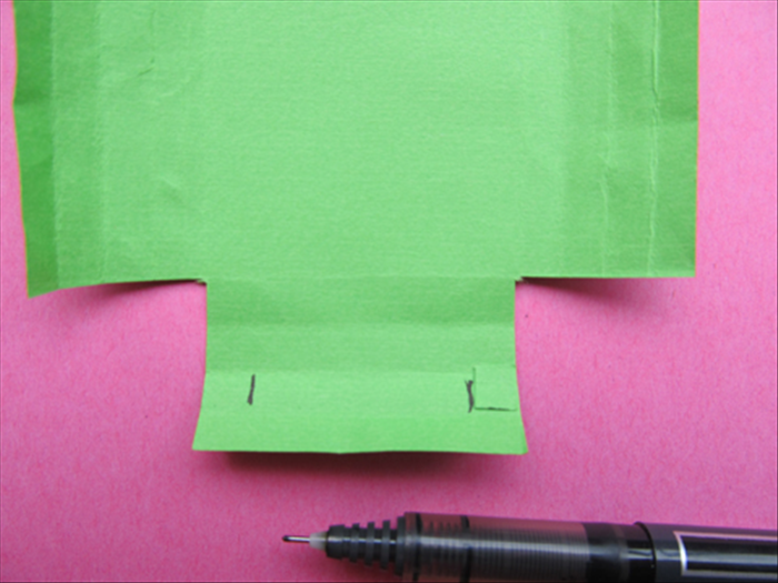Take the measuring square and place it at the outer edges of the second row from the bottom and mark the inner edges with a pen.  Repeat on the top of the paper. Do not mark the sides of the paper.