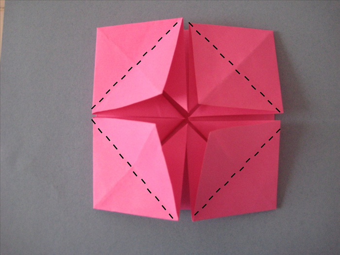 Fold the flaps, you just made, in half by matching the bottom point to the top