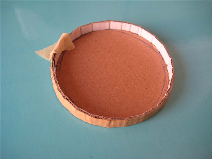 On a flat surface, align the strip around the circle with the glued area touching the outside of the circle.