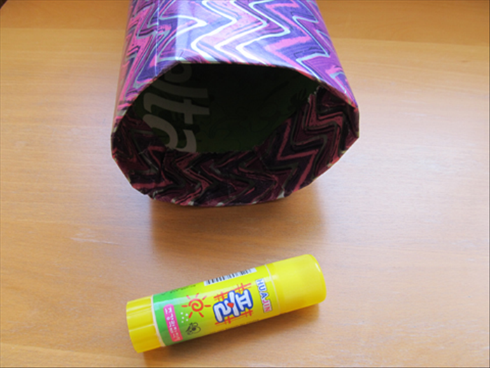 Press all around and straighten it out inside. Glue the paper to the inside of the tube.