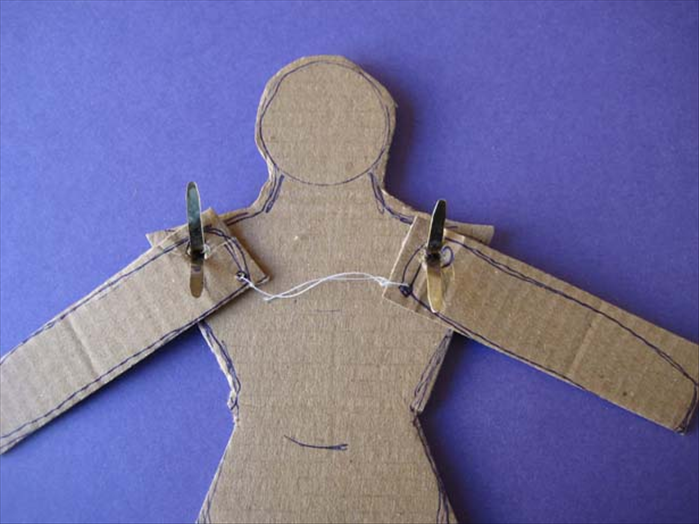 Put paper fasteners through the torso and then the arms.