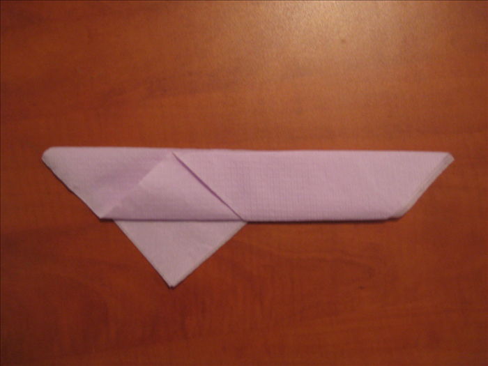 Flip the napkin over to the back side. Place it so that the long edges are at the top and bottom.  Bring the bottom edge up to the top edge. The left point of the layer beneath should stay unfolded.  Bring the point under the right side up from underneath.