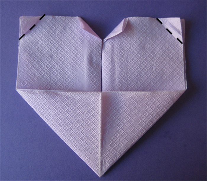 Take the 2 top outer points and fold them down at an angle to the same height.