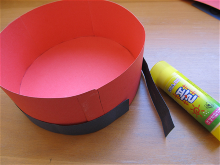 Glue together 1 inch wide strips to be long enough to go around the hat.  Place the circle side of the hat on the table and glue the strip around it.