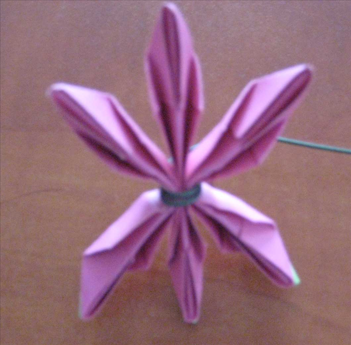 Squeeze the top and bottom  papers in half to create a star shape