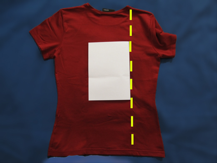 Spread your shirt on a flat surface Rotate the paper so that the folded edge is on the side. Place the paper in the center of the shirt. Bring one side of the shirt over the paper