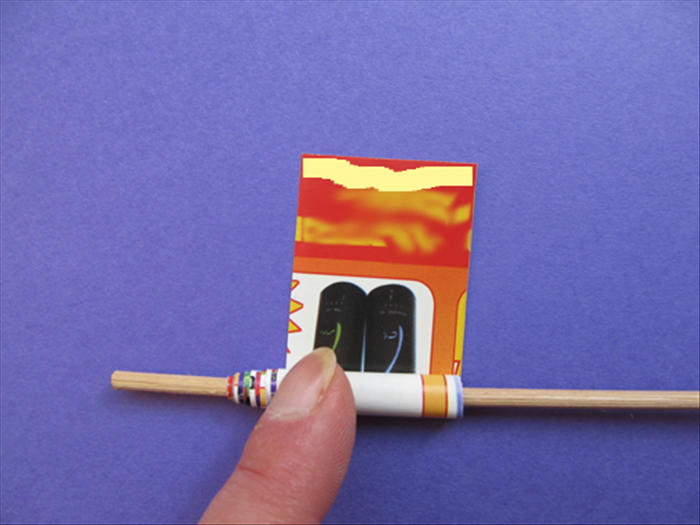 Roll up the strip on the stick. Put glue on the end.