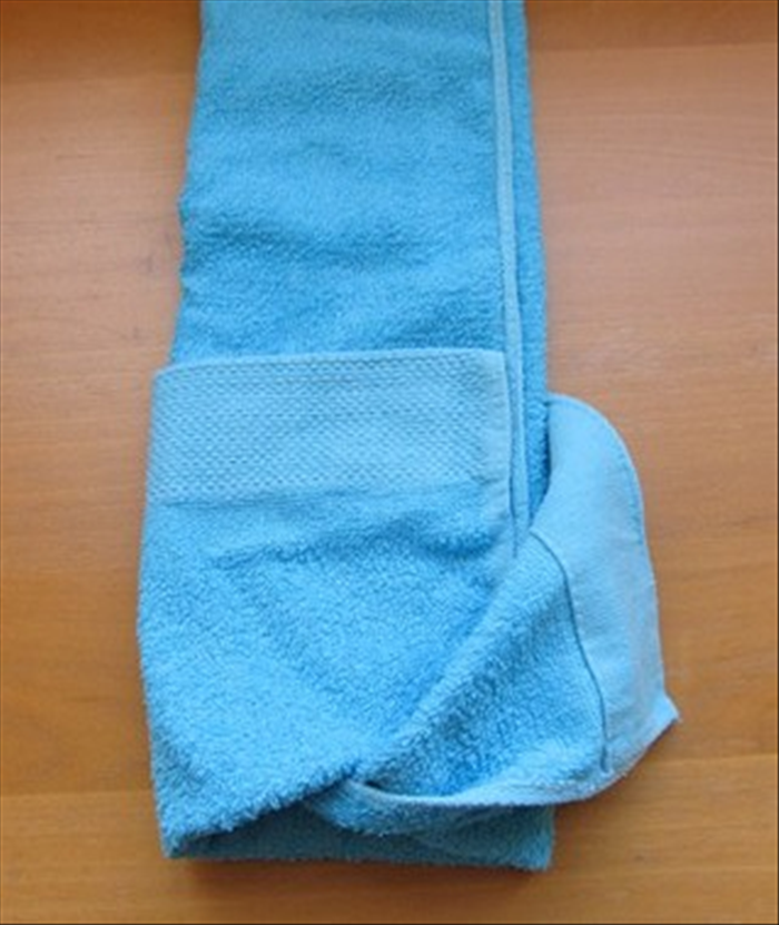 Rotate the towel so that the edge with the pocket is at the bottom.