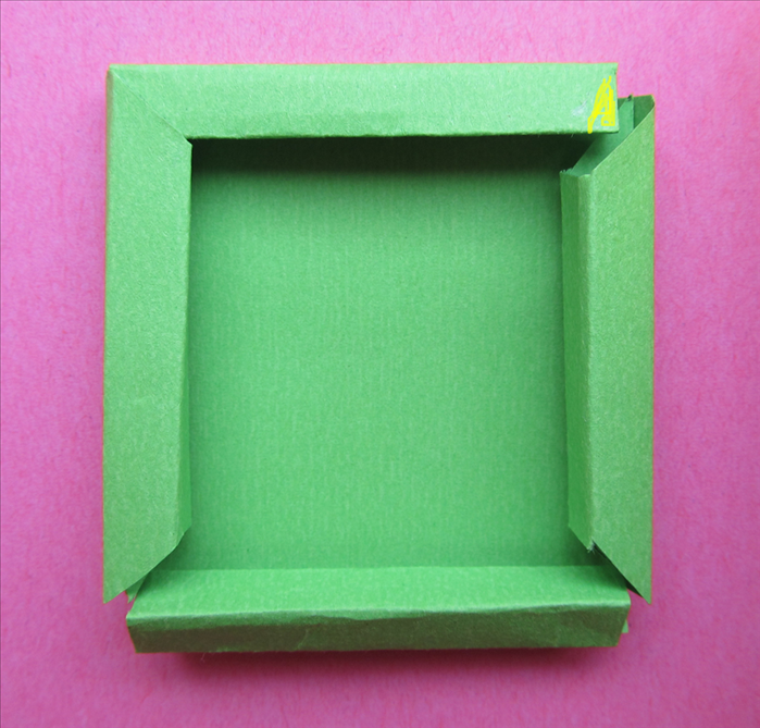 Put glue on the tips of the straight edges and insert them under the slanted edges to form the frame.
