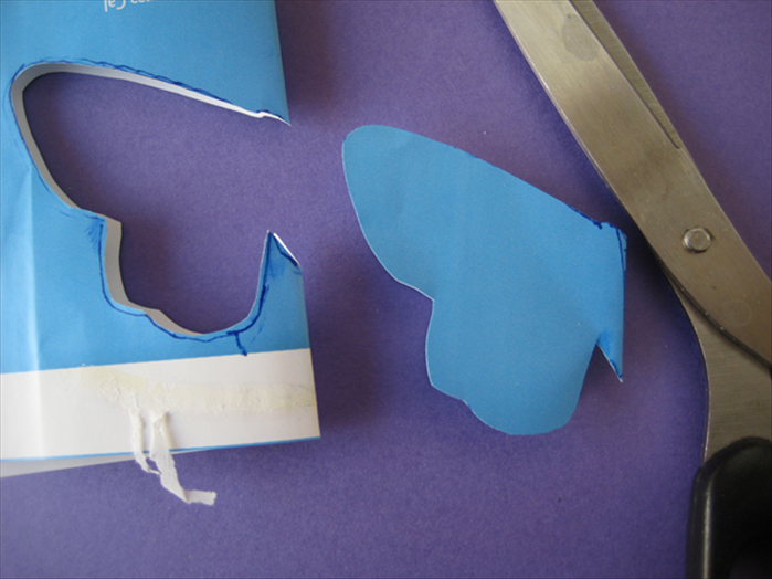 Fold the paper in half and cut out the shape. Cut around the head and tail but do not cut the folded edge.
