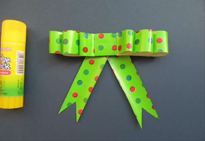 Glue them at an angle to the bottom of the bow.   Your bow is ready to decorate your gift!