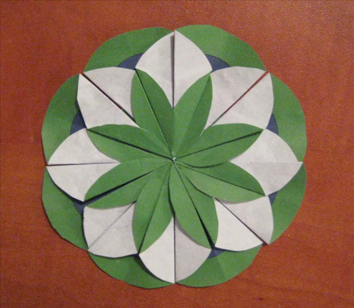 Glue the remaining 4 folded circles in each empty space.  Lift each right flap so that it overlaps the one next to it and your medallion is finished.