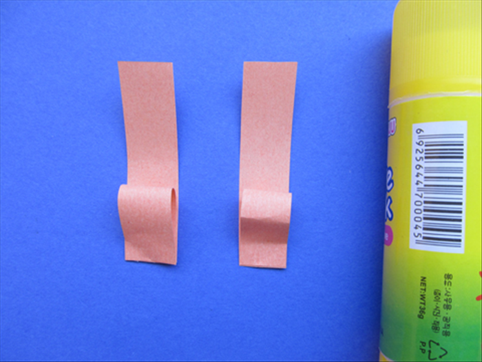 Align the straight edges of the looped strips to the bottoms of the next largest strips and glue them in place – only on the bottom.