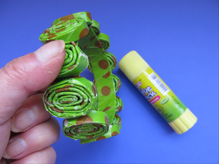 Apply a generous amount of paper glue to the bottom of the rolled paper. Place it on the ring and hold it down a few seconds until it dries. White glue takes too long and it will slide out of place.  If you use hot glue that dries instantly skip the next step.