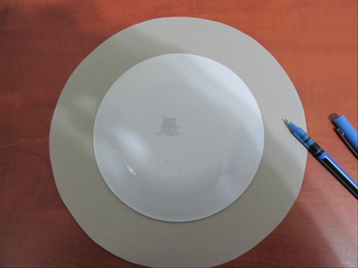 Put the small plate in the center of the large round  cardboard from step 2.