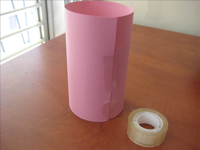 Roll the can in the paper. Stand it on its bottom, adjust the paper so that it aligns with the table and tape the paper closed.