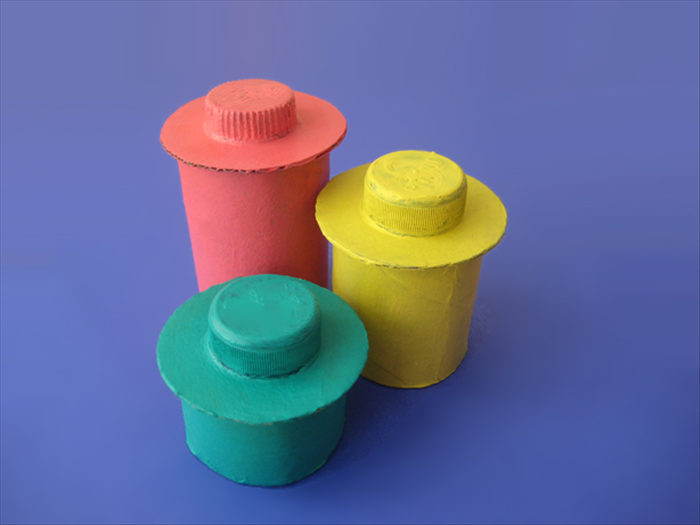 Materials: Toilet paper roll Thick cardboard for the box cover Thin cardboard for the bottom Small bottle cap Plastic glue Scissors Pen 1 round object  with a diameter slightly smaller than the toilet paper roll diameter 1 round object with diameter slightly larger than toilet paper roll diameter