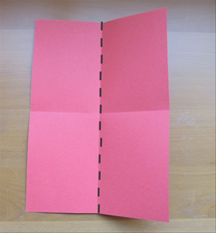Fold the paper in half lengthwise.