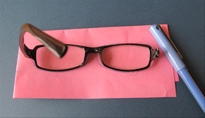 <p> Trace the outline of a pair of glasses on scrap paper.</p>