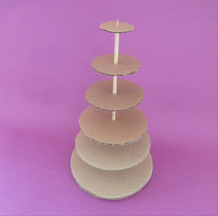 <p> Slide the next largest cardboard circle down the skewer and then a rolled paper with glue on top.</p>  <p> Repeat until you have glued all the circles.</p>  <p> When the glue has dried your cardboard tree will be ready to decorate.</p>  <p> You can stick a star on the point at the top.</p>  <p> Have fun decorating!</p>