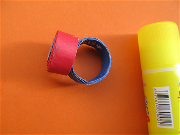 Put a generous amount of glue on the end of the ring and press the coil to it.