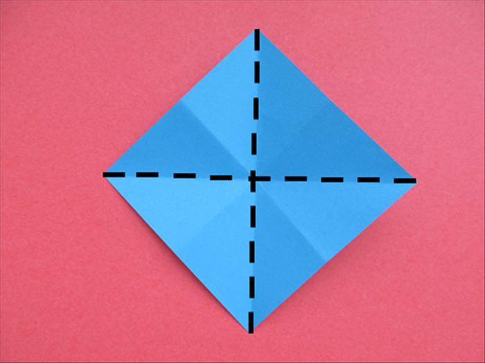 Flip the paper over to the back side with the points at the top, bottom and sides.  Bring the 2 side points together to fold it in half. Unfold Bring the top and bottom points together to fold it in half. Unfold