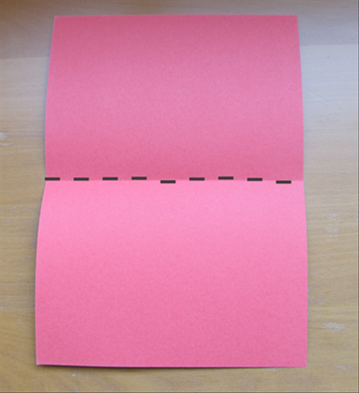 Fold your card paper in half widthwise and unfold.