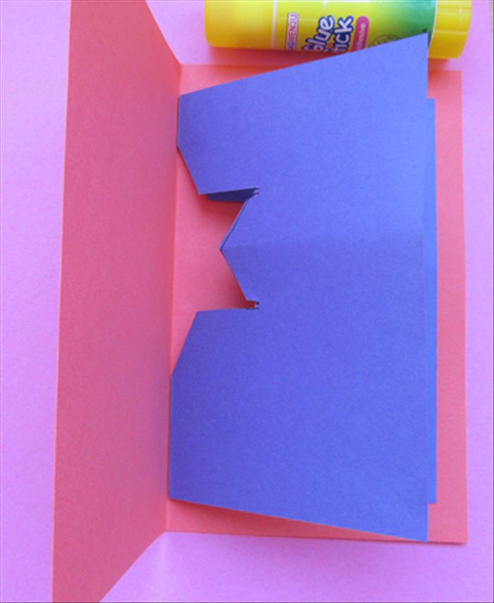 <p> Fold the larger paper in half, align the creases and glue both sides in place.</p>