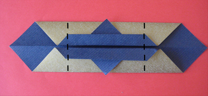 Fold both sides to the back where the straight edge of the little triangles end.