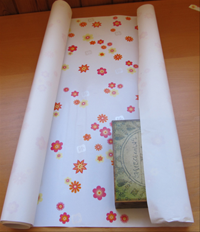 Unroll some of the paper and bring the end to the middle of the gift.