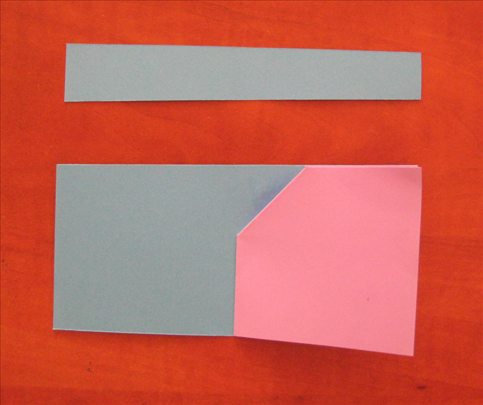Fold the second paper in half. Make a sharp crease and unfold it.  Align the folded edge of the paper with the heart to the crease of the second paper. Glue it in place.  Cut a straight line across off of the top, using the top of the heart paper as a guide..