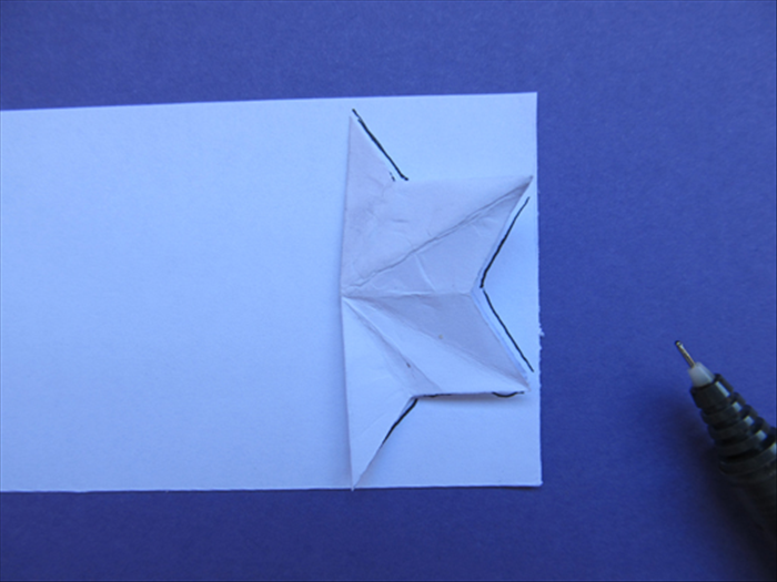 Place the half star on the edge of the paper strip as shown Trace the outline of the points up to the fold