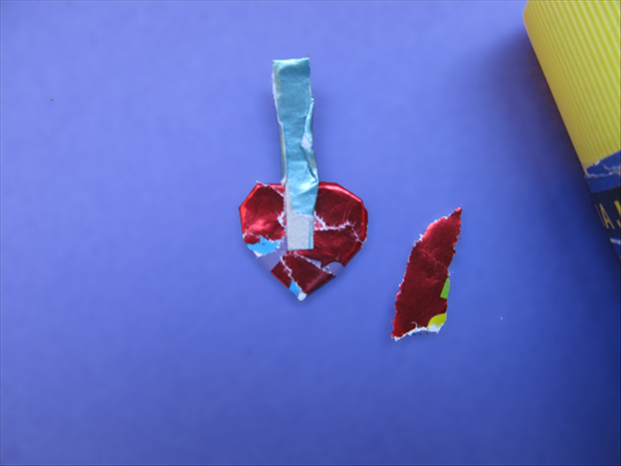 <p> Cover the heart with paper.</p>  <p> Cut a thin strip and cover it with the same color paper as the bottom of the house.</p>  <p> Glue it to the heart and cover it with the same color paper as the heart.</p>  <p>  </p>