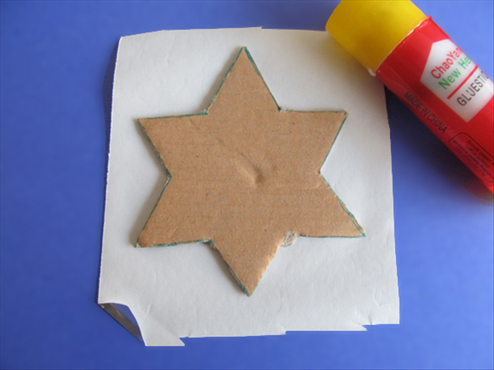 <p> Glue the cardboard star to the back of colored paper.</p>  <p> Here silver colored paper was used. </p>  <p> Cut the paper along the edges of the star.</p>  <p>  </p>