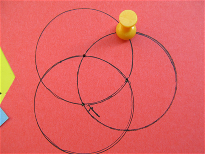 Push a pin in where the circle you just made touches the first circle.  Remove the pin