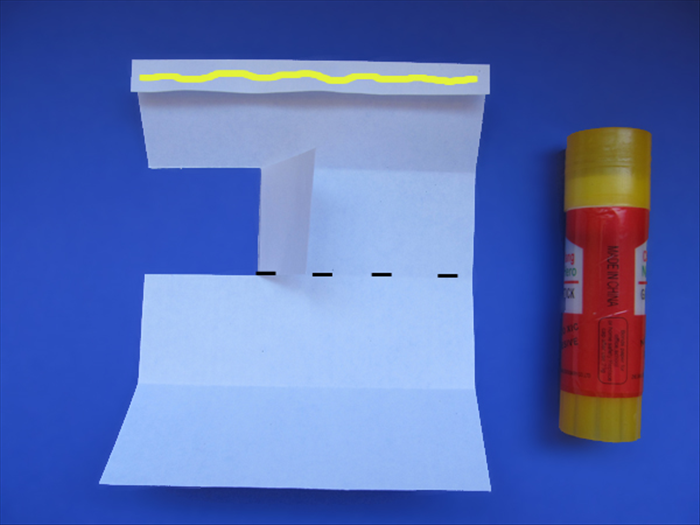 <p> Flip the paper over. The folded edge should be on top.</p>  <p>  </p>  <p> Fold the flap over.</p>  <p> Put glue on the folded edge.</p>  <p> Bring the bottom edge up to the top edge to fold the paper in half.</p>   <p> Let the glue dry.</p>   <p>  </p>
