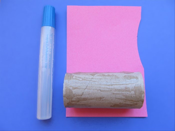 Coat the toilet paper roll with glue