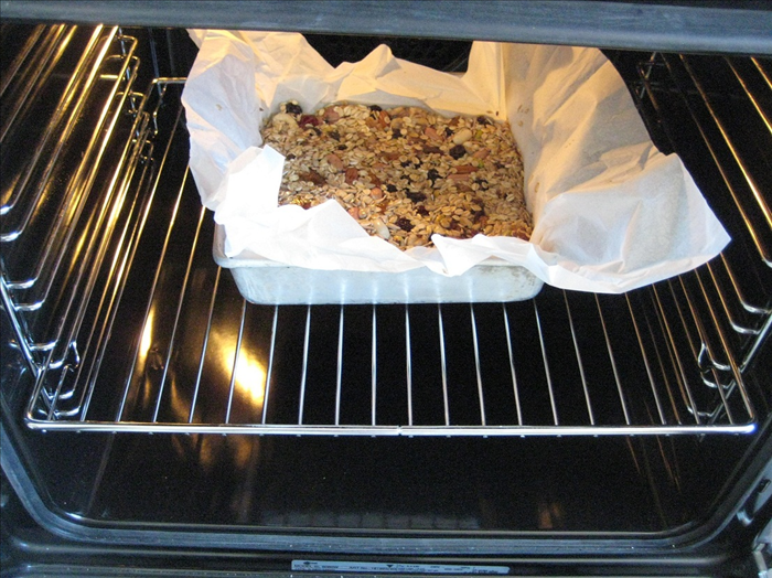 Oil a baking pan and put a layer of parchment paper in it. Pour the mixture into baking pan.  Use a piece of the parchment paper to  press down the mixture evenly into the pan.    Bake for 25 to 30 minutes, until light golden brown.   *Check to make sure it does not burn