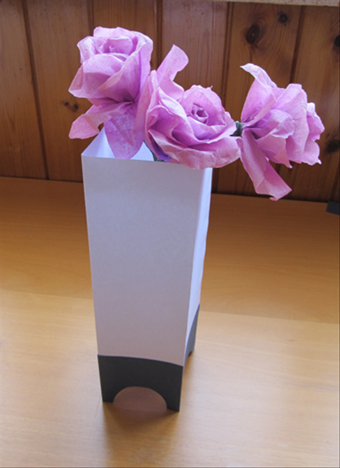 <p> Materials:</p>  <p> 1 peice of sturdy paper twice the height of the width - * This is a tall thin vase.  To make it shorter make the height of the paper shorter.</p>  <p> 1 different color piece of sturdy paper the same width but 1/4 the height</p>  <p> Round object</p>  <p> Scissors</p>  <p> Paper glue</p>  <p> Pen or penci</p>