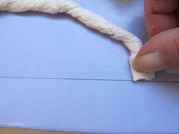 Cut the other end of the tissue paper rope and align it to the drawn line.