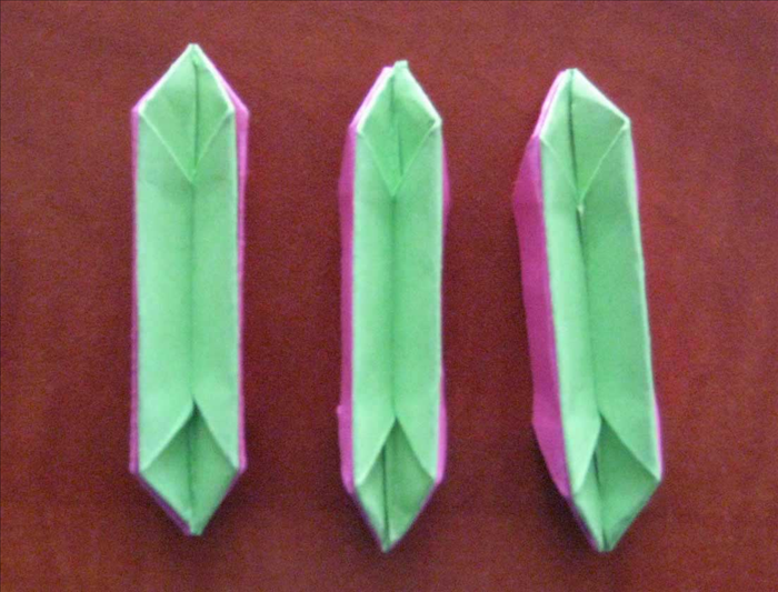 Place the 3 green papers inside of the 3 pink ones