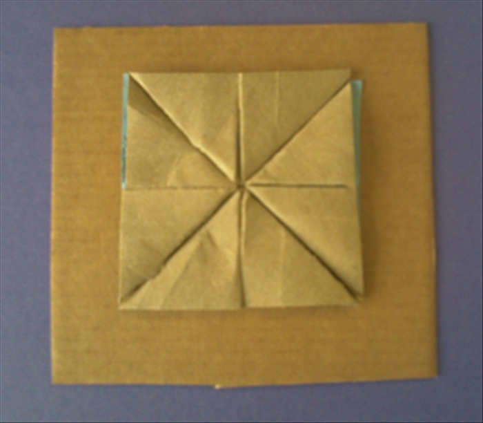 Glue 4 brown triangles on the center of the square cardboard