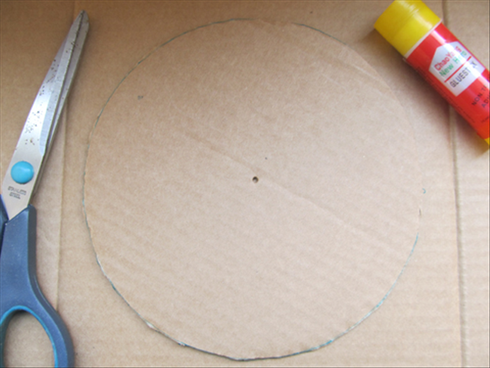<p> Take one of the cutout circles and trace the outline on cardboard.</p>  <p> Cut out the circle.</p>  <p> Now you have 4 circles with a hole in the center and the one circle you just traced without a hole in the center.</p>  <p>  </p>