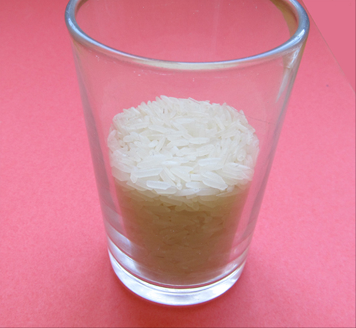 Pour ½ cup of rice or other small grains into a glass
