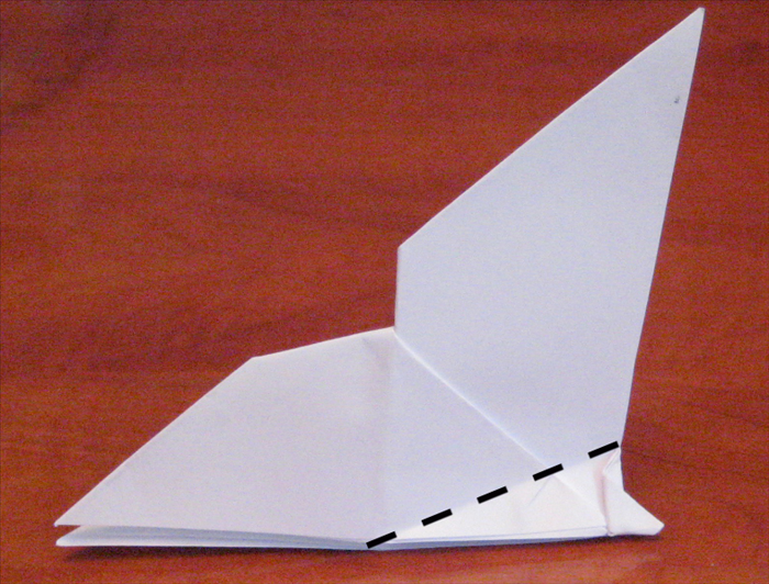 Fold a wing down at an angle. Flip the paper over and repeat on the other side. Make sure the folded wings are aligned.
