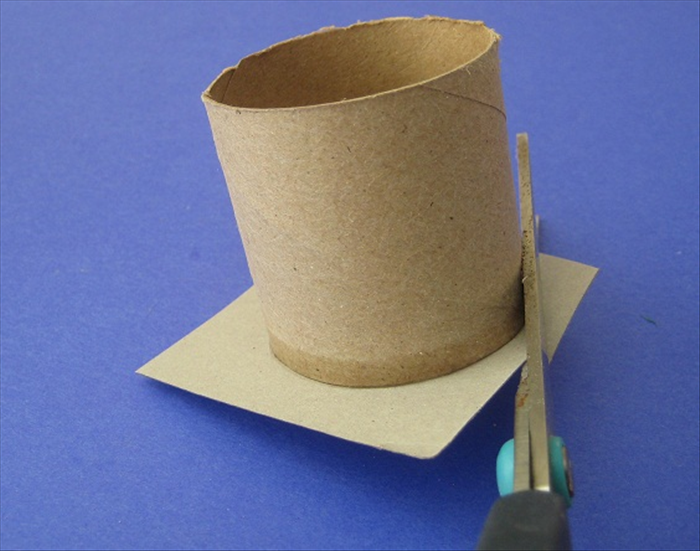 Make sure the glue has dried and then cut around the toilet paper roll.