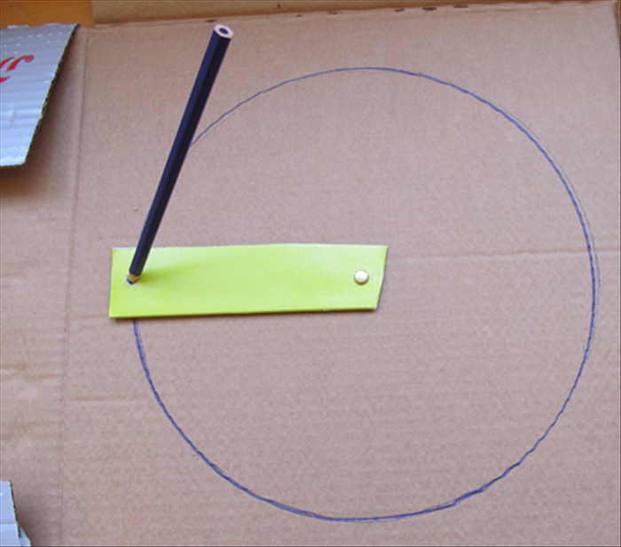 Use the paper fastener to attach one end of the cardboard strip to the center of the cardboard you want to draw on. 