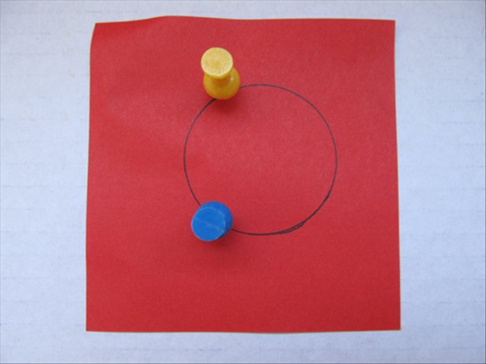 Put the paper on top of the scrap cardboard. Push the 2 push pins on the line of the circle opposite each other as shown in the picture.
