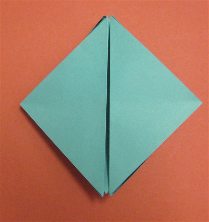 Stick your fingers between the 2 flaps at the center and pull them up.
