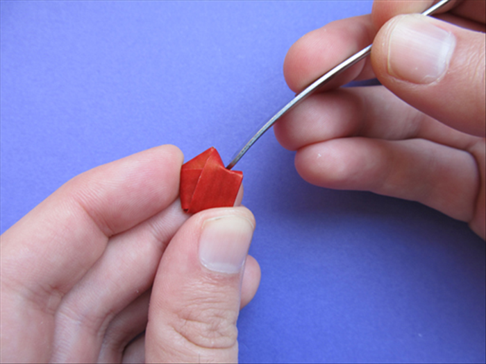 Hold the pentagon shape with your thumb at the flat bottom and your pointer finger at the point opposite it. Use the flat edge of a spoon or your finger nail to push in the side